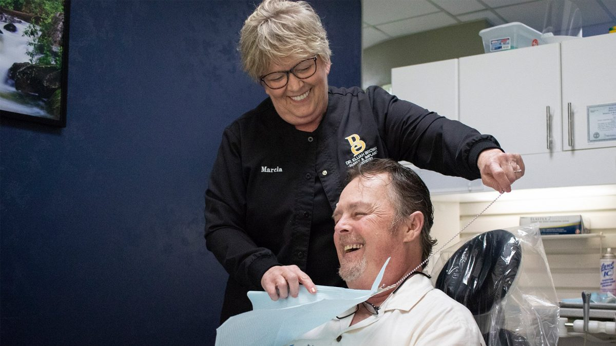 patient smiling with hygienist as she puts on bib